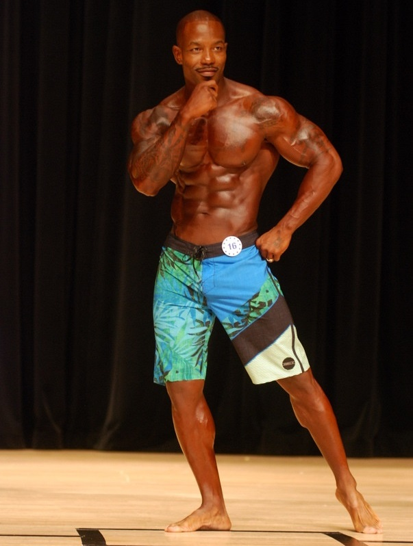 Antoine Williams posing on the Men's Physique stage, looking aesthetic and ripped