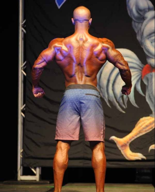 Antoine Williams displaying his back muscles in a men's physique competition