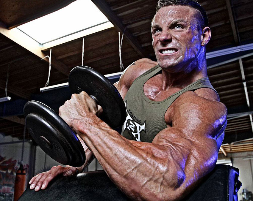 Brad Rowe performing dumbbell curls in the gym.