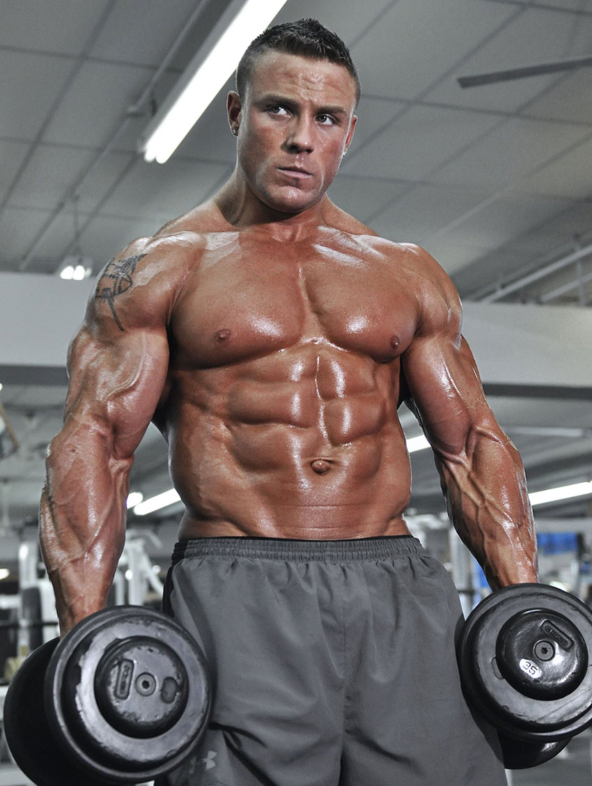 Brad Rowe holding dumbbells in a photo shoot.