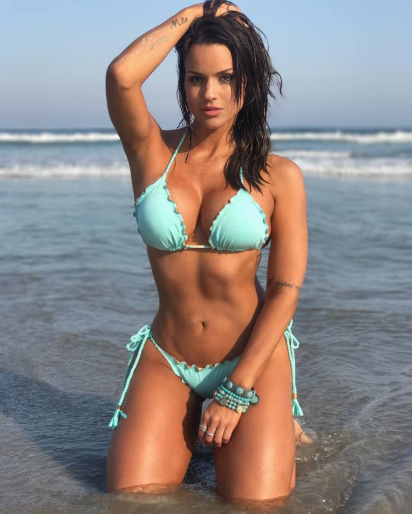 Carol Dias kneeling on the beach and looking at the camera