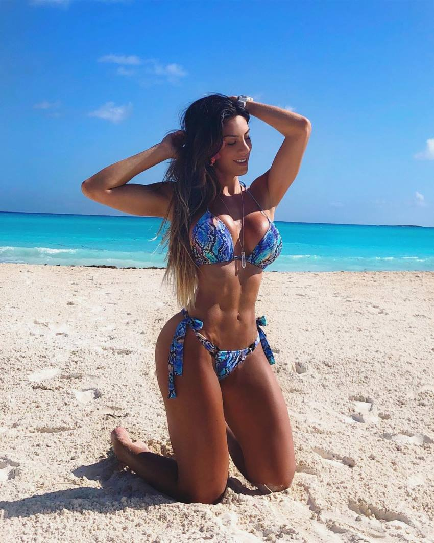 Carol Saraiva kneeling on the sand by the beack looking healthy and lean