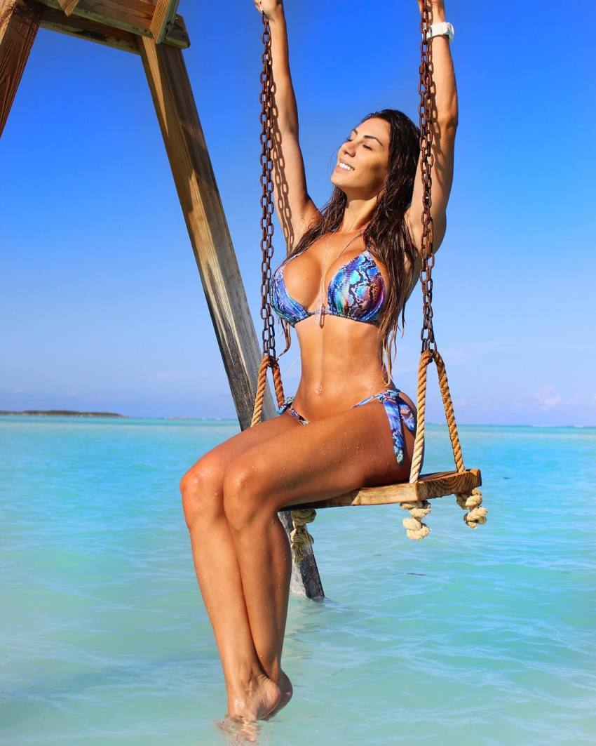 Carol Saraiva on a swing by the sea, looking fit and lean