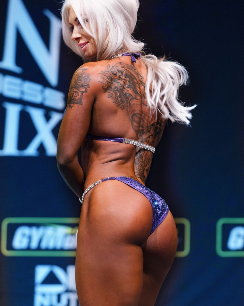 Caroline Aspenskog standing on the bikini stage, showing her tones glutes and back to the judges