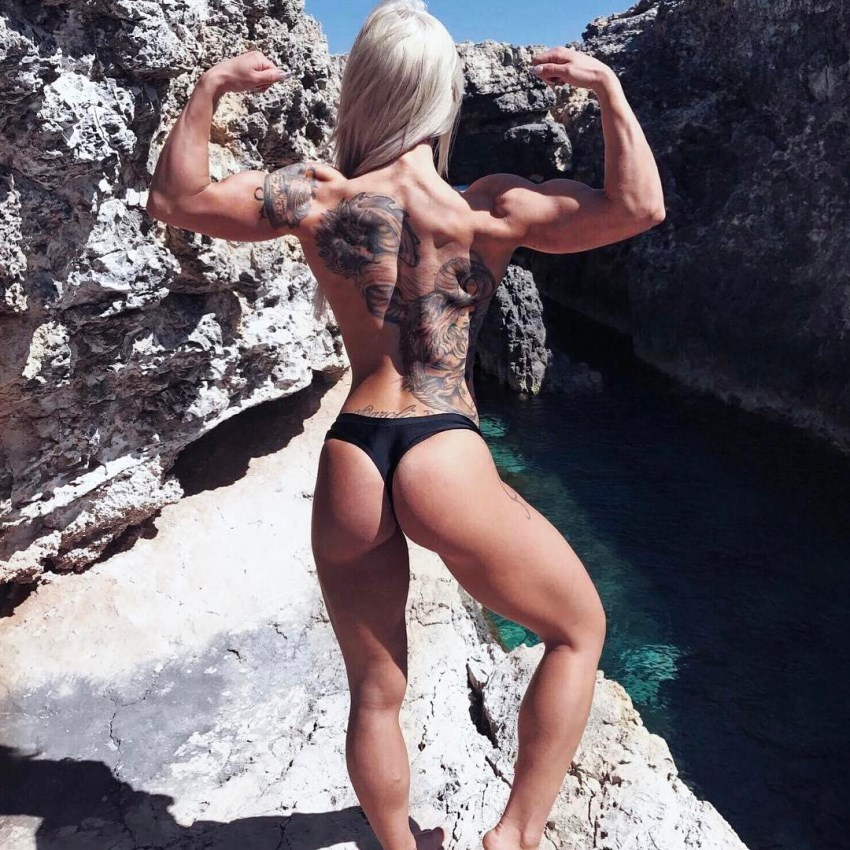 Caroline Aspenskog shirtless outdoors, showing a back double biceps pose for the camera