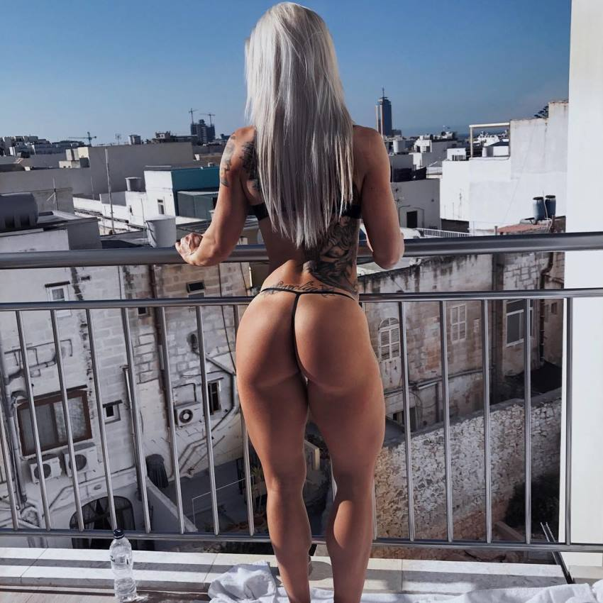 Caroline Aspenskog standing on a balcony, showing her awesome glutes and legs