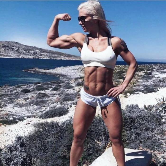 Caroline Aspenskog flexing her muscular biceps in sunny outdoors