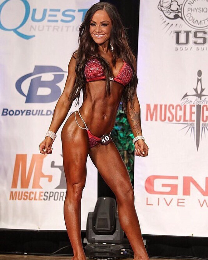 Caryn Nicole Paolini on the bikini stage smiling at the judges