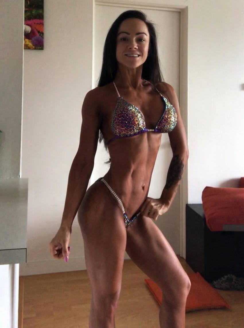 Caryn Nicole Paolini posing in a bikini, looking ready to step on the stage