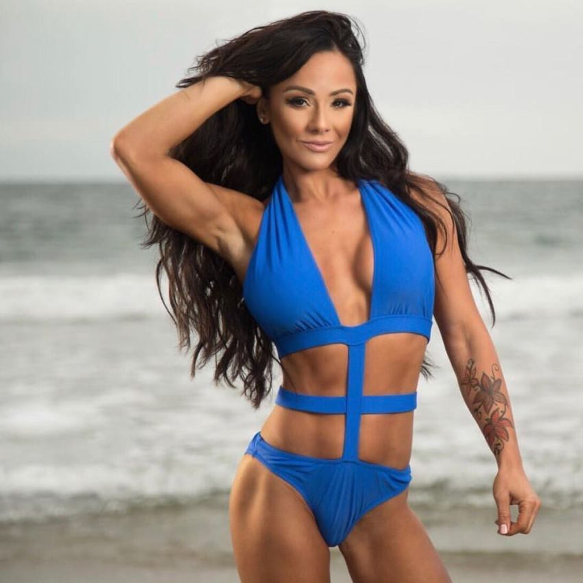 Caryn Nicole Paolini posing on the beach in a blue swimsuit