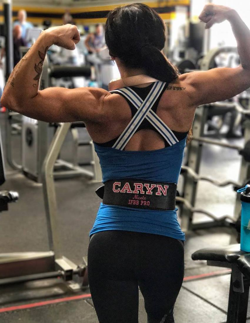 Caryn Nicole Paolini doing a back double biceps pose in the gym