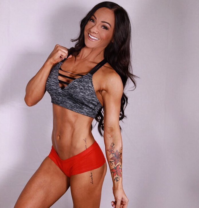 Caryn Nicole Paolini smiling and flexing her abs for the photo