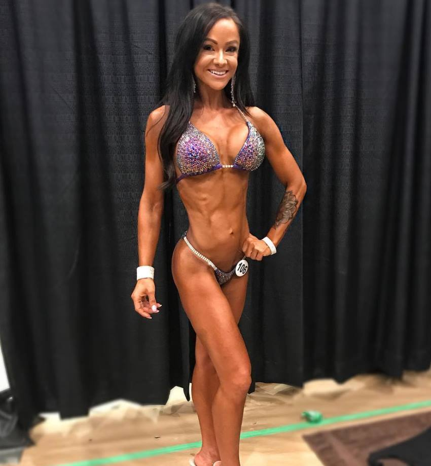 Caryn Nicole Paolini posing in a bikini backstage, looking conditioned and aesthetic