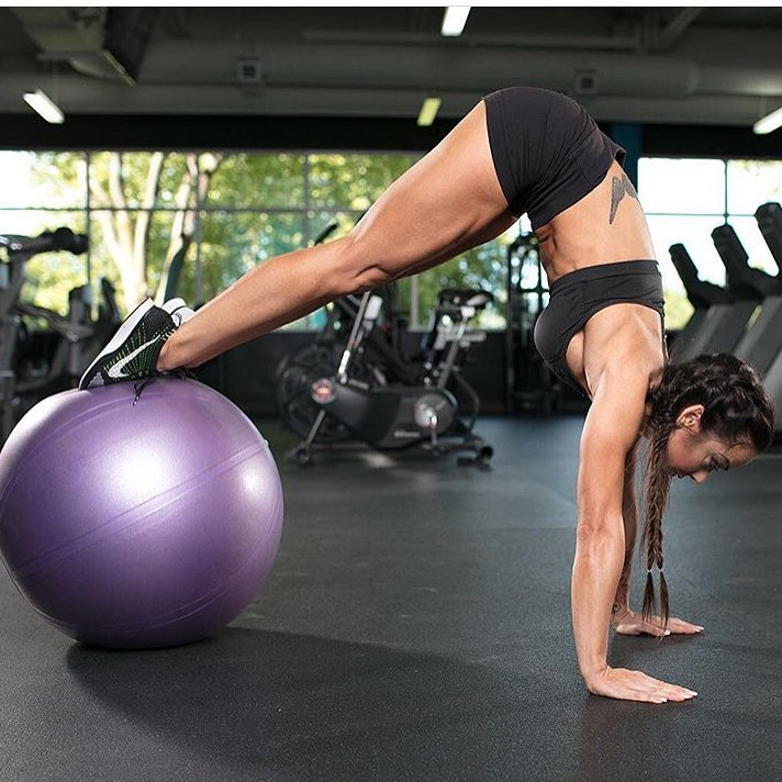 Caryn Nicole Paolini doing an exercise on a medicine ball