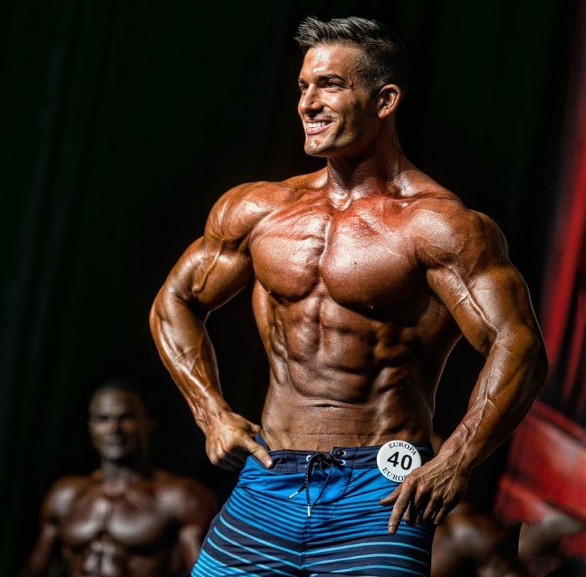Chase Savoie posing on the bodybuilding stage.