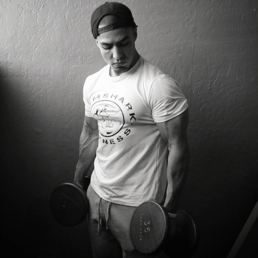Chris Lavado holding dumbbells in a photo shoot.