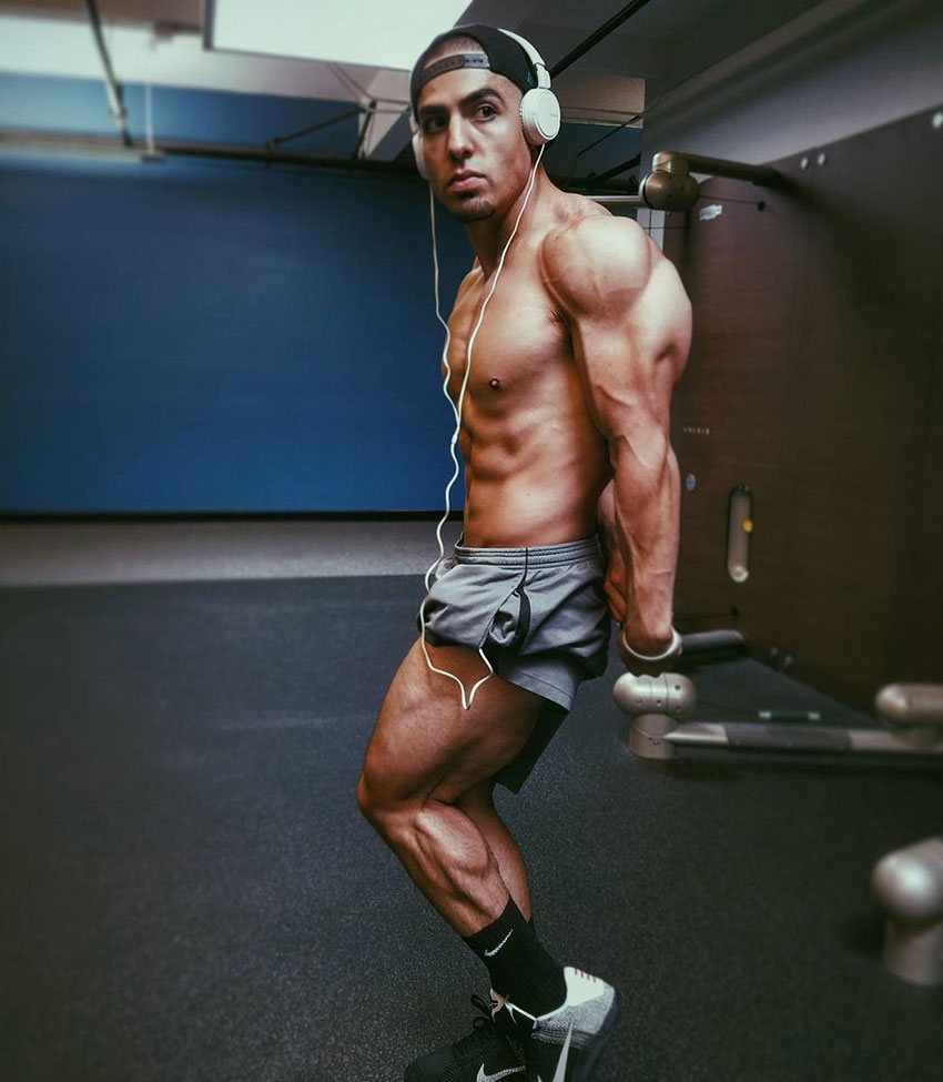 Chris Lavado posing, showing off his physique in the gym.
