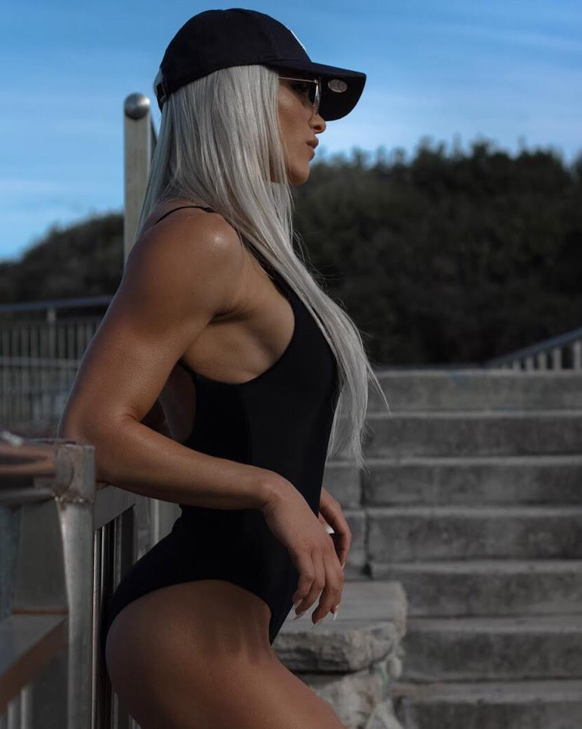 Side picture of Christine Ray posing and showing off her lean and muscular arms