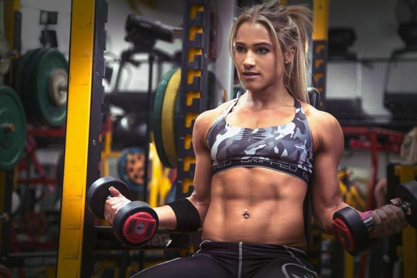 Christine Ray lifting dumbbells in the gym, her abs looking lean and fit