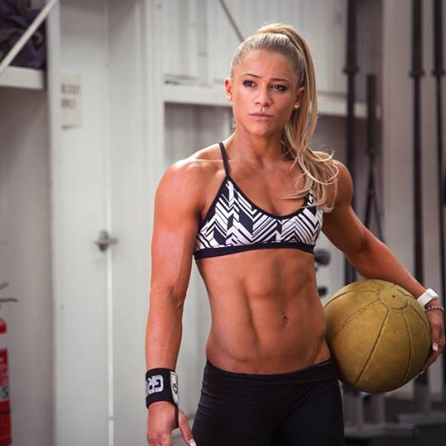 Christine Ray holding a ball in her hand, looking fit and ripped