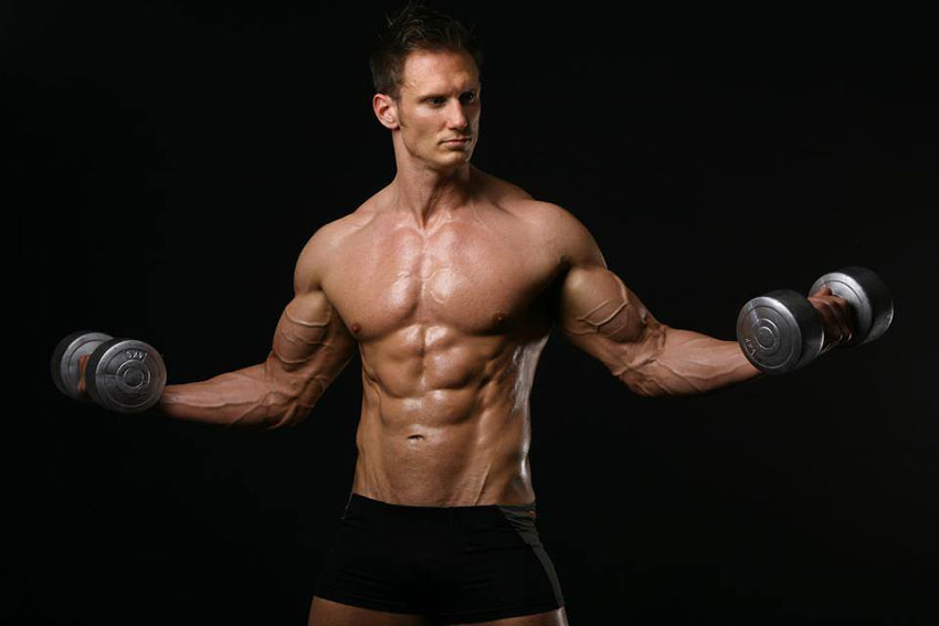 Dave Cunningham holding dumbbells in a photo shoot.