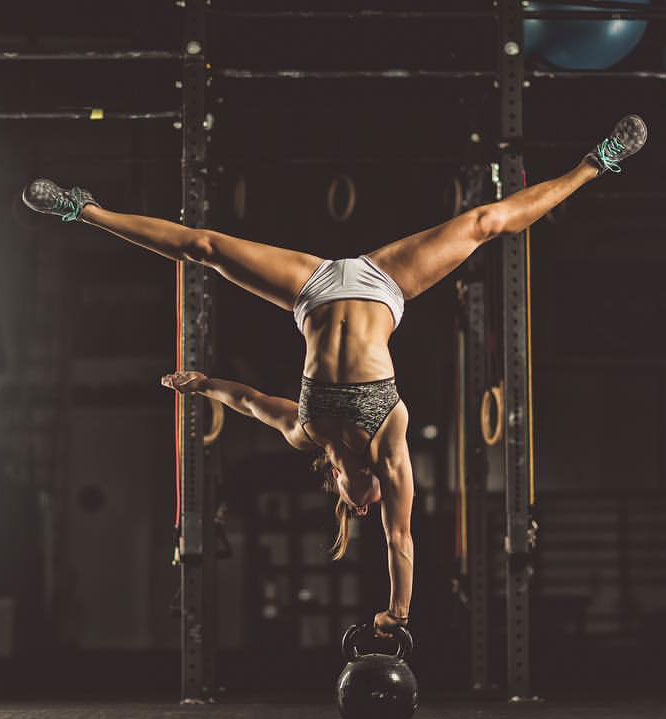 Demi Bagby holding onto a kettlebell while upside down.