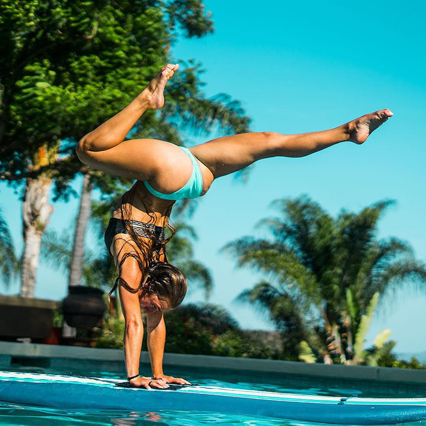 Demi Bagby performing a handstand by a swimming pool.