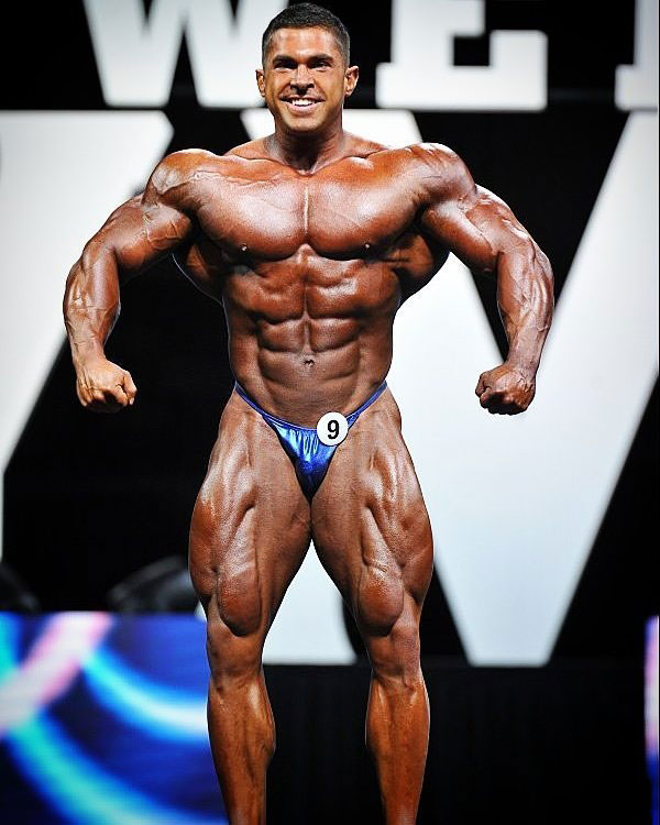 Derek Lunsford posing on the bodybuilding stage.