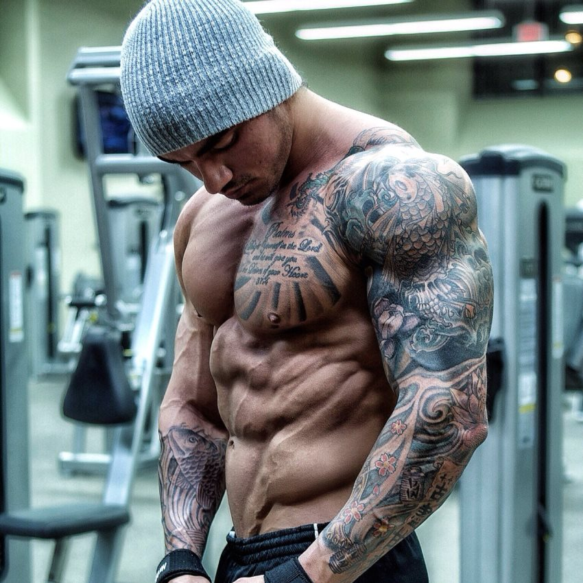 Devin Physique posing shirtless in a grey hat for a photo, looking ripped and muscular