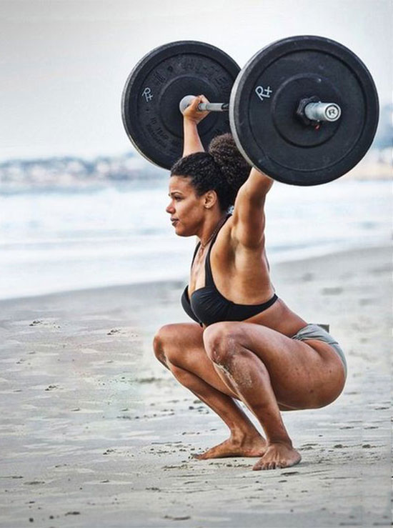 Elizabeth Akinwale training with a barbell on the beach.