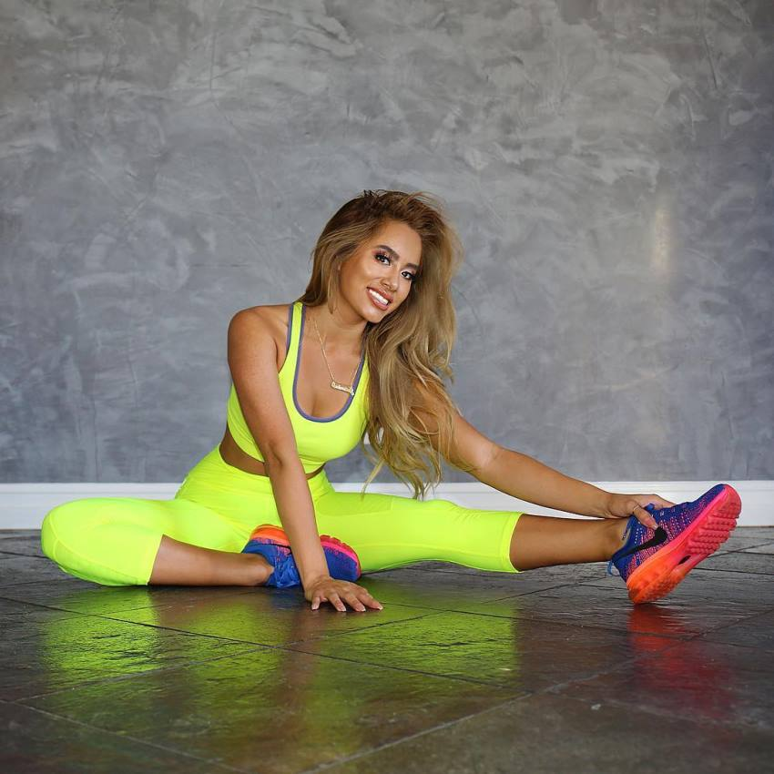 Jasmine Chiquito stretching and smiling at the camera, wearing bright green leggings and sportsbra