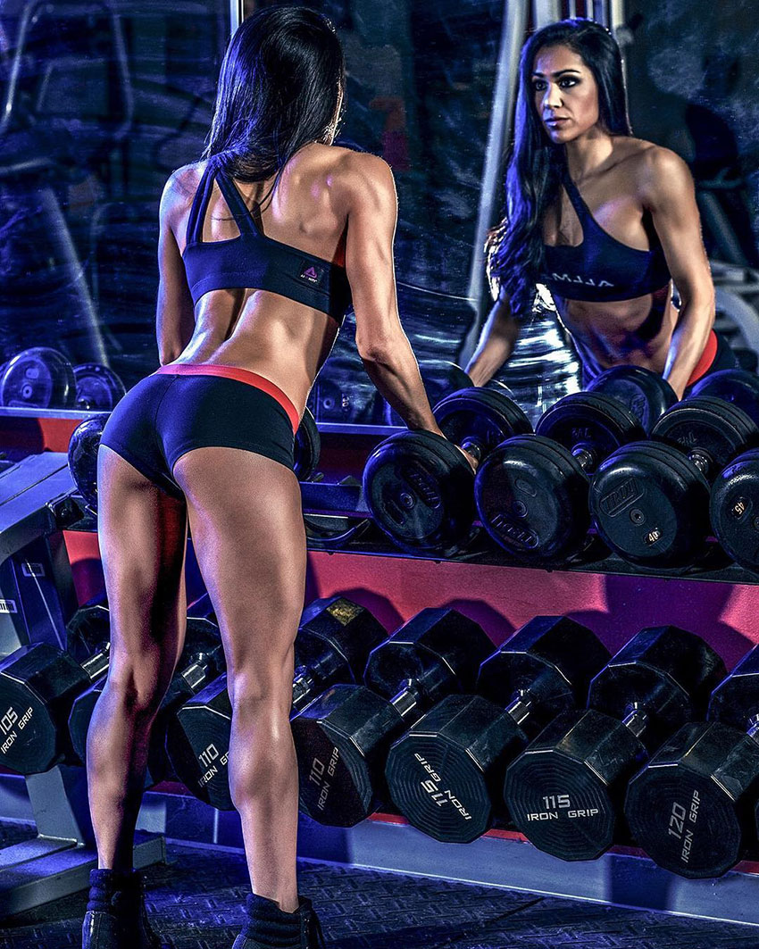 Jennifer Ronzitti stood next to a dumbbell rack looking into a mirror.