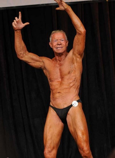 Jim Arrington performing a posing routine on a bodybuilding stage.