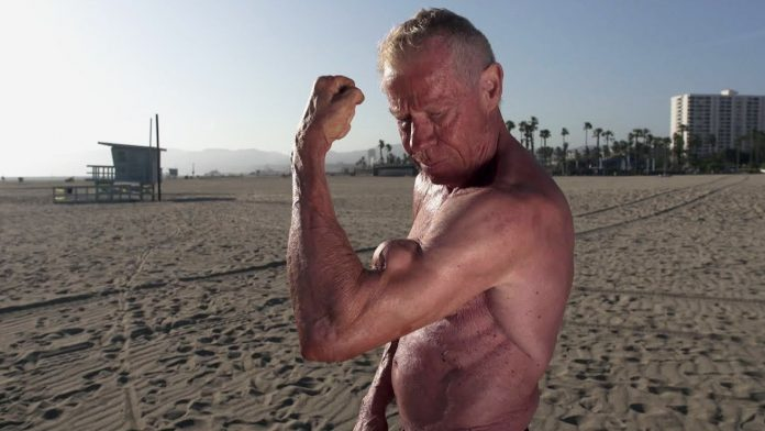 Jim Arrington shirtless on the beach, showing off his remarkable biceps peak