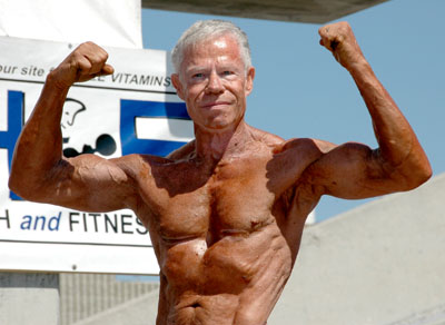 Jim Arrington posing shirtless outdoors, doing a front double biceps flex