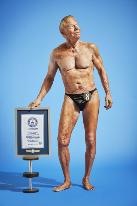 Jim Arrington standing by his Guinness World Record for being the oldest male bodybuilder in the world
