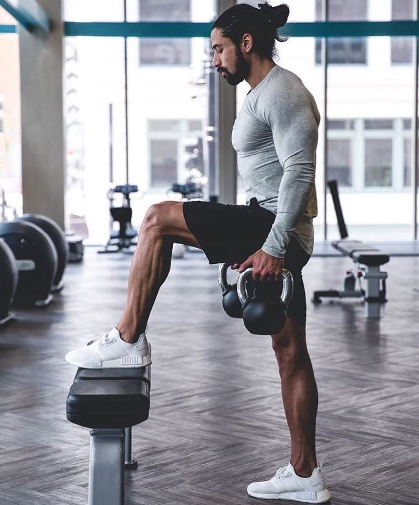 Justin Gonzales doing lunges on a bench lookin fit