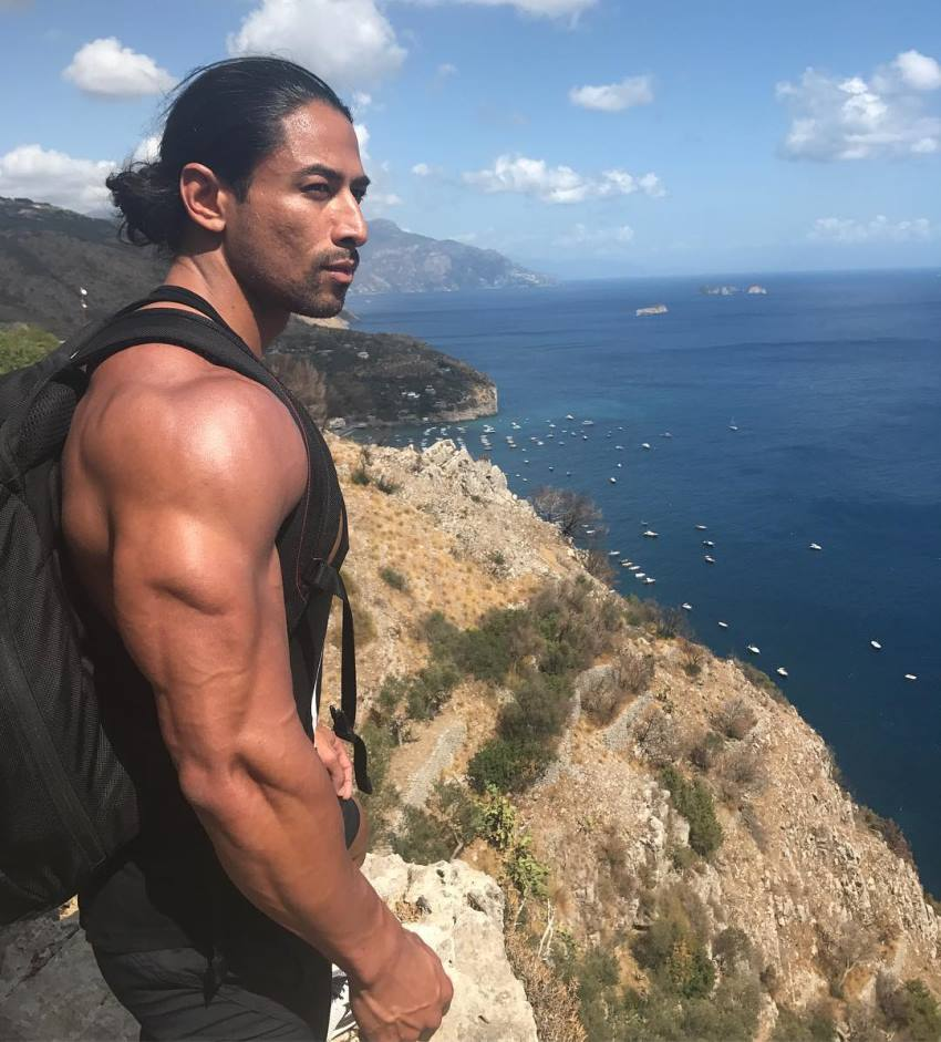 Justin Gonzales standing on the edge of a cliff overlooking a sea