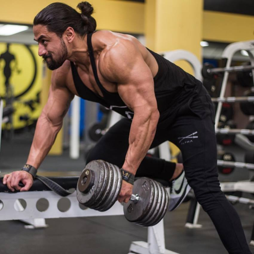 Justin Gonzales doing dumbbell bent-over rows, looking ripped and muscular