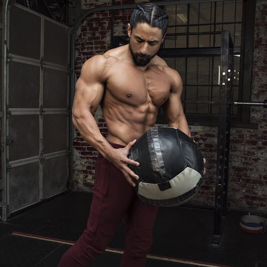 Justin Gonzales holding a ball and showcasting his ripped physique