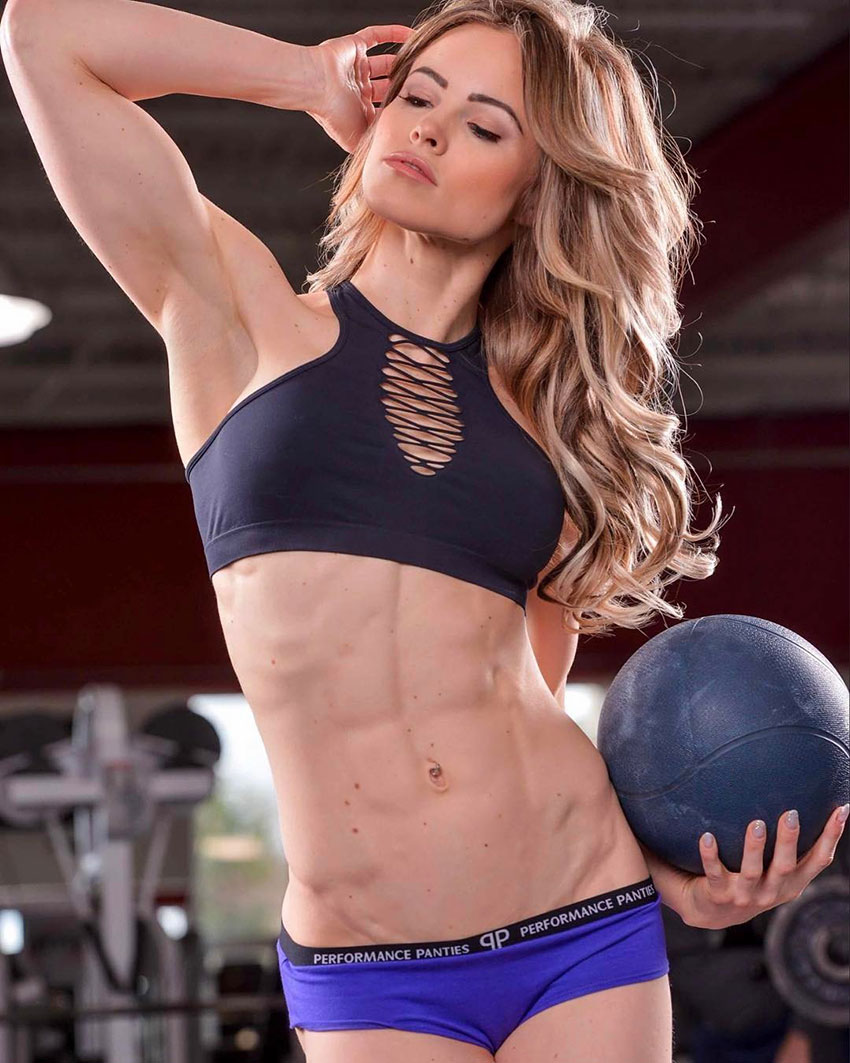 Justine Munro showing off her abs, holding a medicine ball.