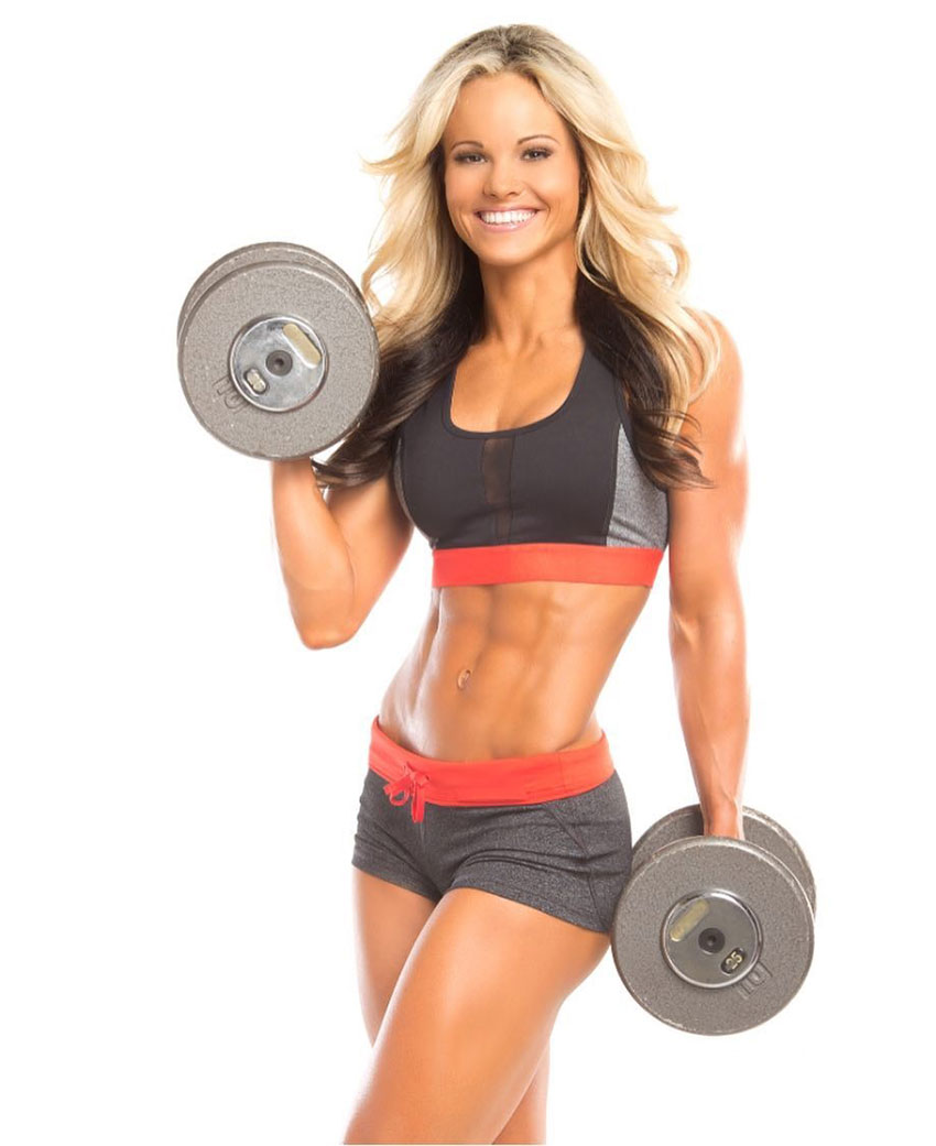 Justine Munro holding dumbbells in a photo shoot.