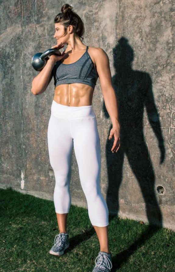 Katie Sonier holding a kettlebell in a photo shoot.