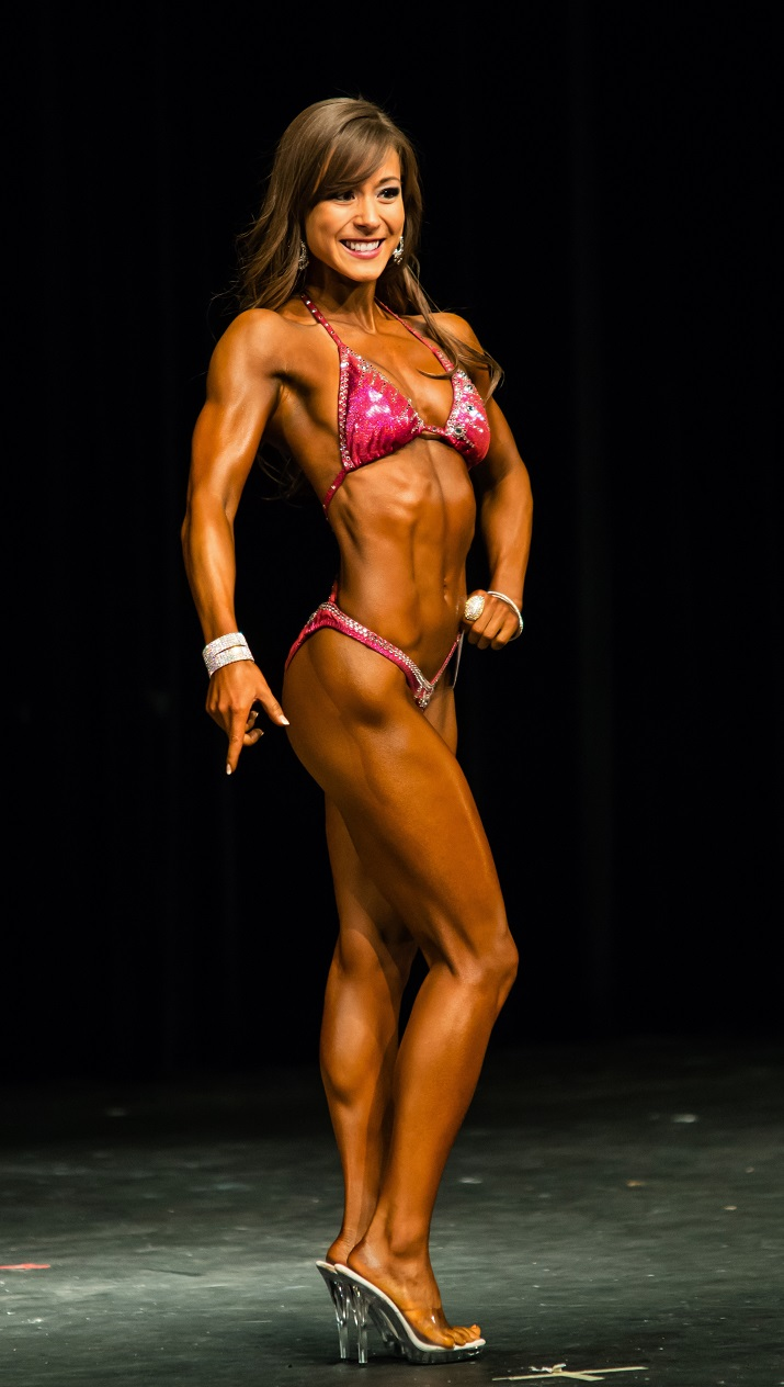 Kimberly Marie doing a side pose on the fitness stage looking conditioned