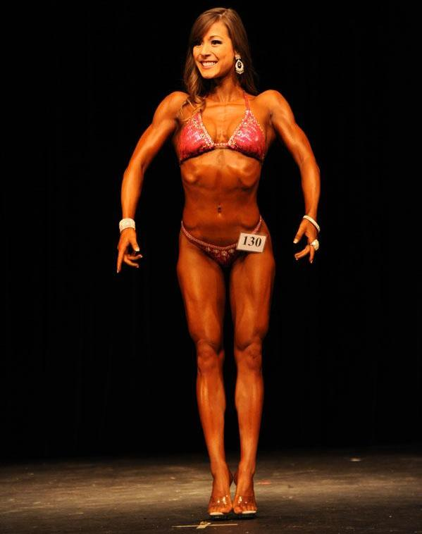Kimberly Marie posing on the stage showing off her lean and muscular physique