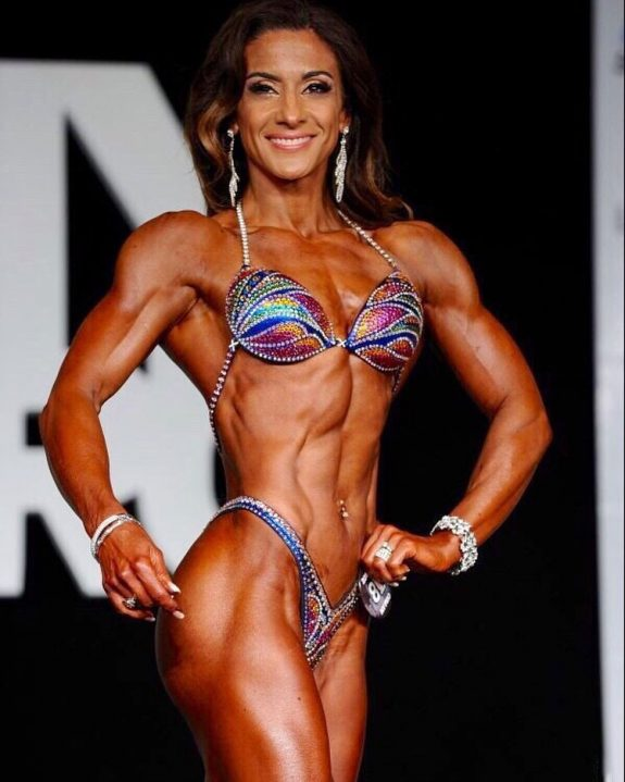 Maggie Corso posing on the bodybuilding stage.