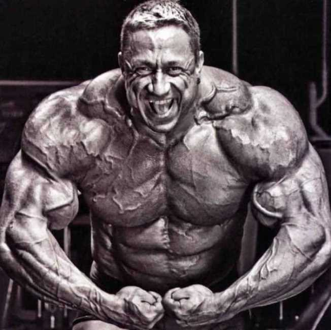 Markus Ruhl looking straight at the camera while doing a most muscular pose, looking incredibly massive and ripped
