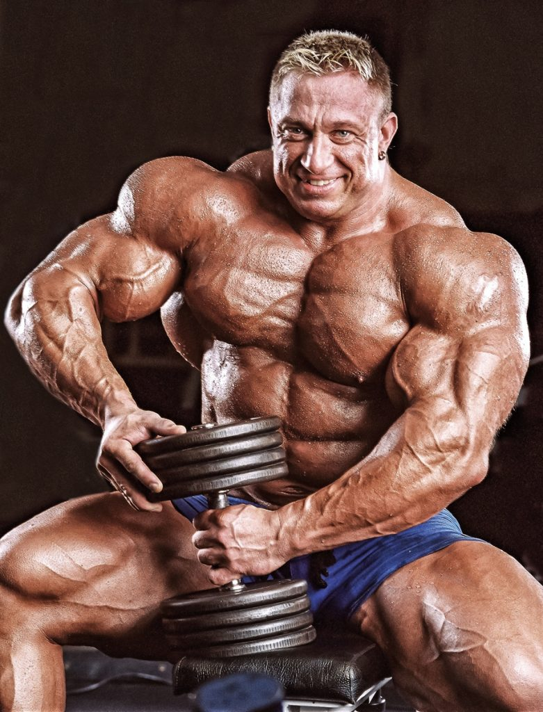 Markus Ruhl posing shirtless with a dumbbell in his hand, looking muscular and ripped