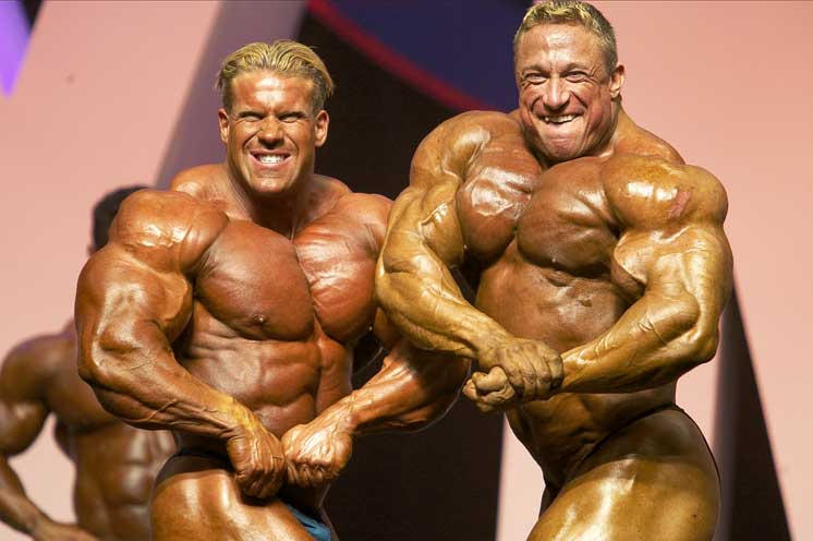 Markus Ruhl doing a side chest pose on the stage standing Next to Jay Cutler