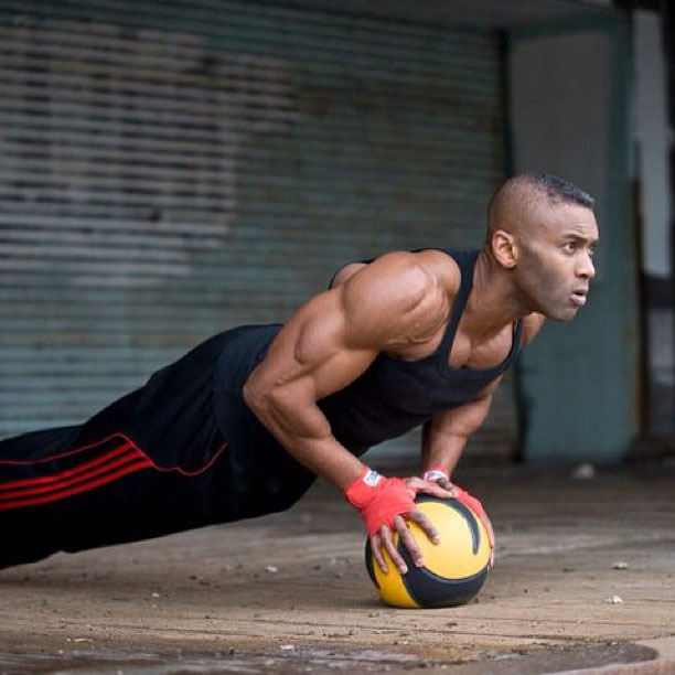 Michael Anderson balancing his weight using his arms on a medicine ball.